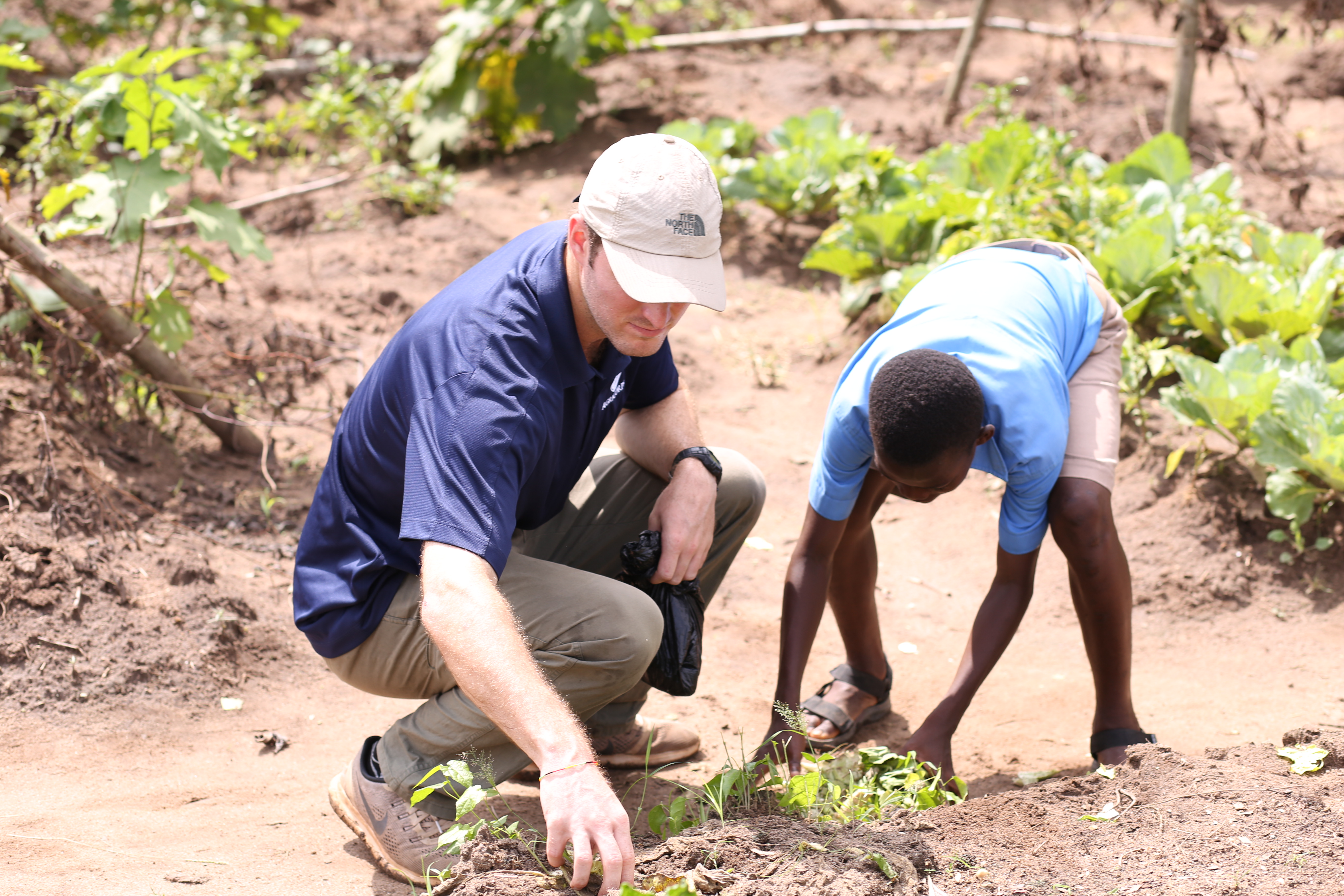 Ryan Tomlin and a student pull weeds